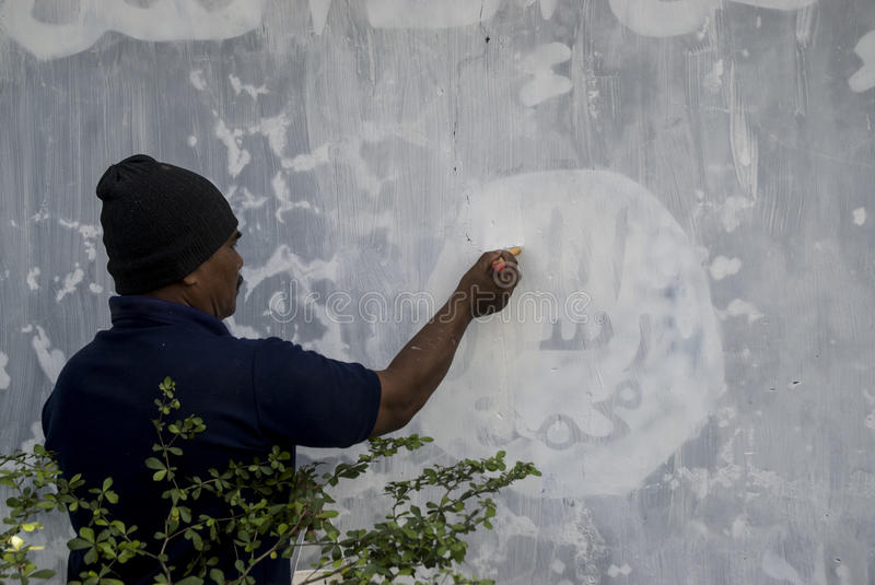 INDONESIA ISLAMIC STATE WAR. Government officials erase an Islamic State graffiti on a street side wall at Solo, Java, Indonesia. Indonesian President Joko stock image