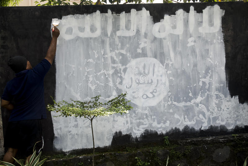 INDONESIA ISLAMIC STATE WAR. Government officials erase an Islamic State graffiti on a street side wall at Solo, Java, Indonesia. Indonesian President Joko stock photo