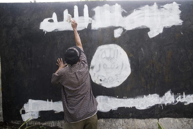 INDONESIA ISLAMIC STATE WAR. Government officials erase an Islamic State graffiti on a street side wall at Solo, Java, Indonesia. Indonesian President Joko royalty free stock photo