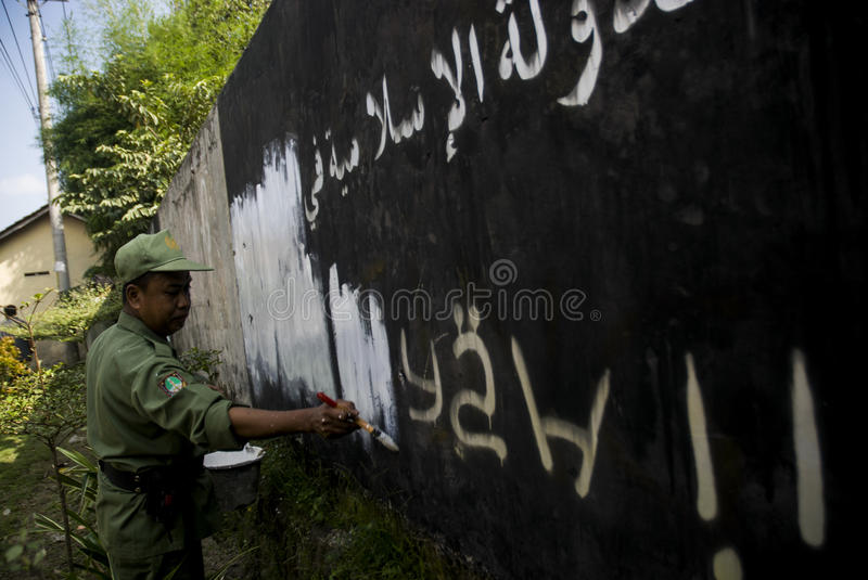 INDONESIA ISLAMIC STATE WAR. Government officials erase an Islamic State graffiti on a street side wall at Solo, Java, Indonesia. Indonesian President Joko royalty free stock photography