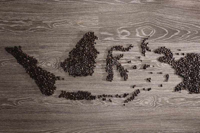 Indonesia map with coffee beans. With wooden background royalty free stock image
