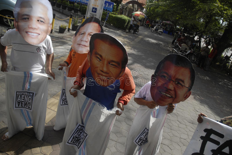 INDONESIA TIGHTEST PRESIDENTIAL ELECTION. Supporters use mask of Presidential candidate on a sack running race game, to call for fair play on the election, in royalty free stock image