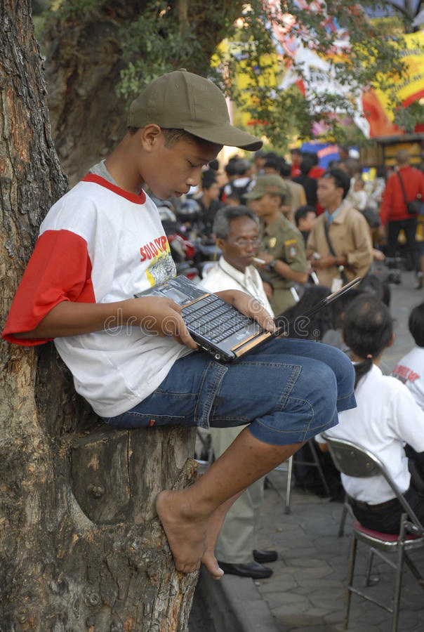 INDONESIA TO RAISE TECH FUND. A boy are accessing internet via WiFi hot spot using laptop or notebook computers at the street of Solo, Java, Indonesia royalty free stock photo