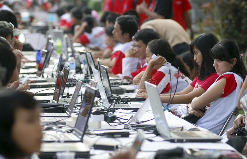 INDONESIA TO RAISE TECH FUND. A girl are accessing internet via WiFi hot spot using laptop or notebook computers at the street of Solo, Java, Indonesia royalty free stock photography
