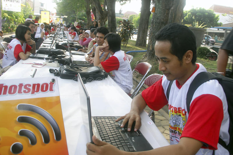 INDONESIA TO RAISE TECH FUND. People are accessing internet via WiFi hot spot using laptop or notebook computers at the street of Solo, Java, Indonesia stock photos
