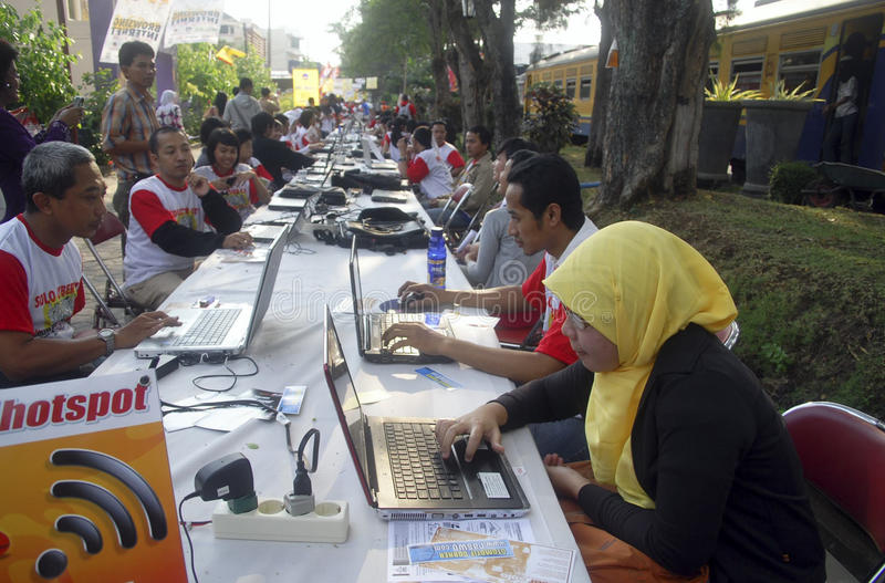 INDONESIA TO RAISE TECH FUND. People are accessing internet via WiFi hot spot using laptop or notebook computers at the street of Solo, Java, Indonesia stock image