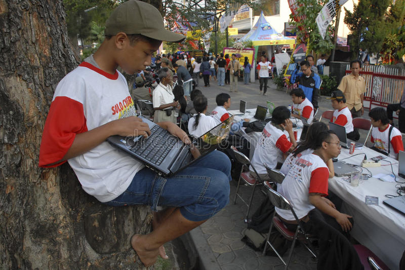 INDONESIA TO RAISE TECH FUND. People are accessing internet via WiFi hot spot using laptop or notebook computers at the street of Solo, Java, Indonesia stock images