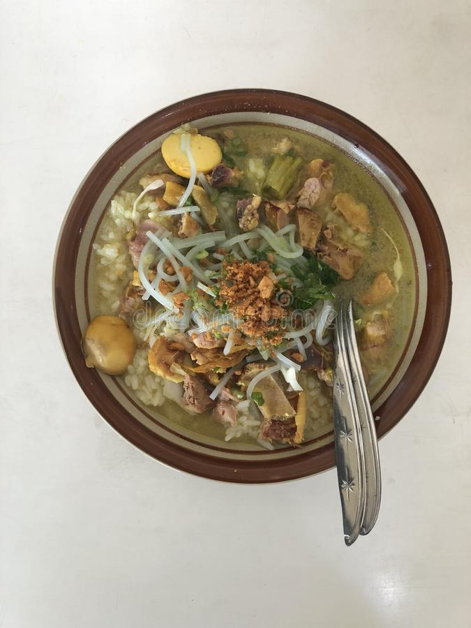 Soto ayam Lamongan or Lamongan chicken soup. Indonesia traditional chicken soup serve with egg stock image