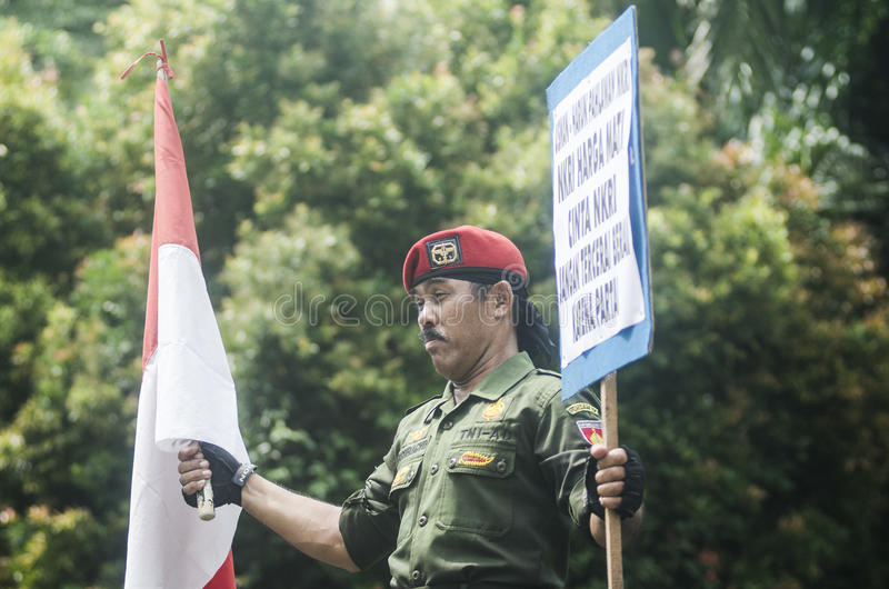 INDONESIA WORLD BANK OFFER. A soldier holds Indonesian National Flag The Red and White at Solo, Java, Indonesia. The World Bank offered up to $11 billion in new stock images