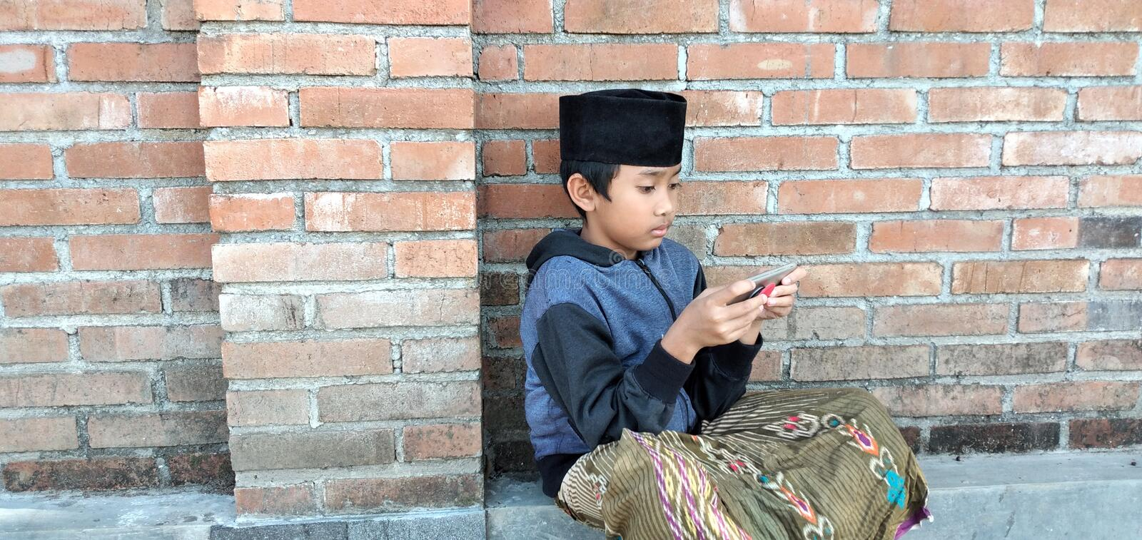 Indonesian boys play mobile phones on the home page. stock photography