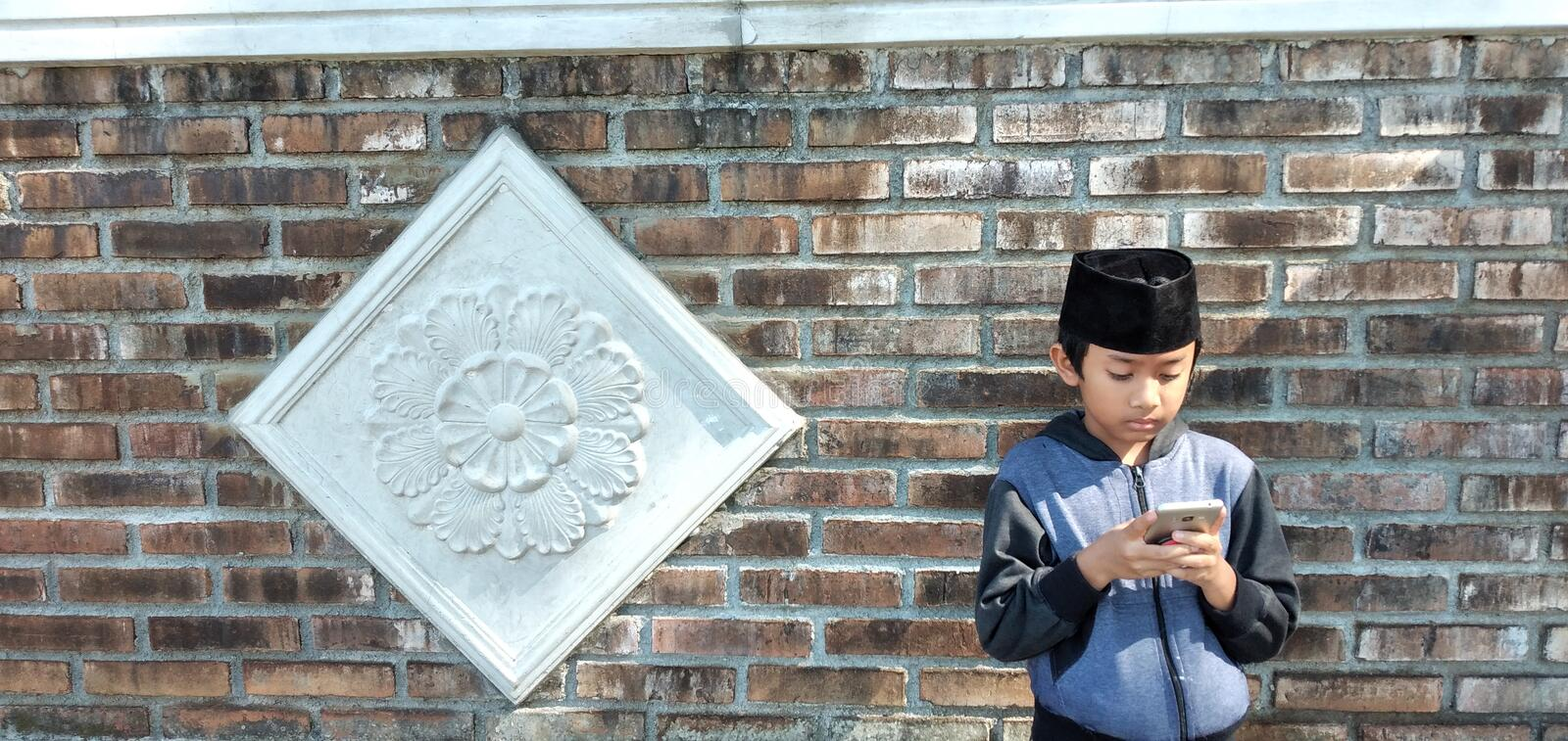 Indonesian boys play mobile phones on the home page. royalty free stock image