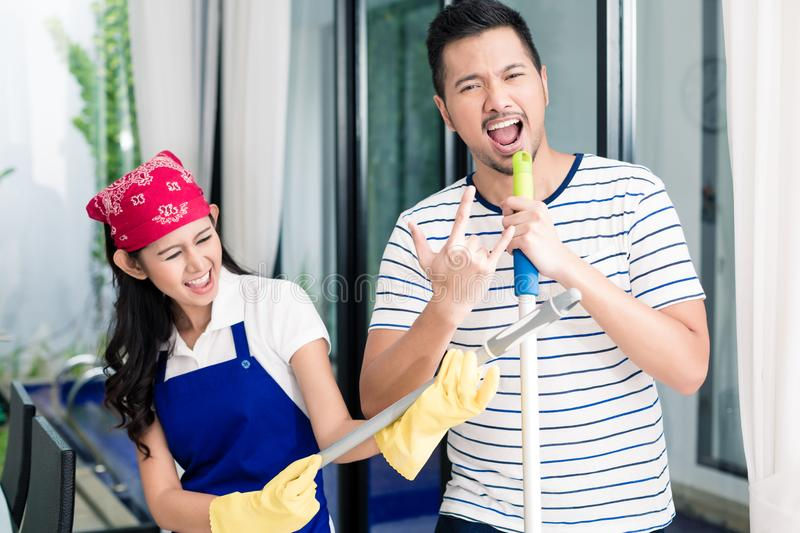 Indonesian couple having fun cleaning the home. Women and men playing air guitar on duster and broom royalty free stock photos