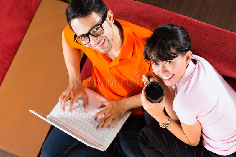 Asian couple on the couch with a laptop. Indonesian couple sitting home on sofa with laptop using the internet for email and online shopping royalty free stock photos