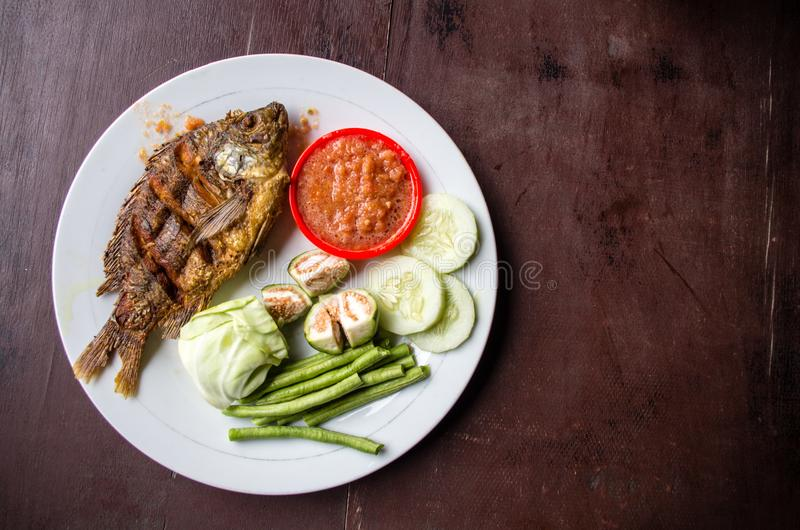Indonesian dish ikan goreng fried fish with copy space right.  stock image