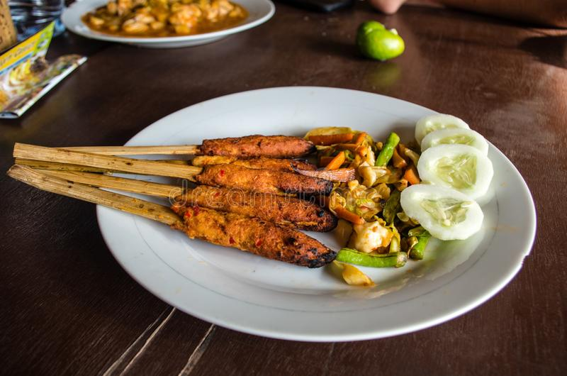 Indonesian dish Lombok: Sate Pusut marinated meat mix on stick on table with other dishes in background royalty free stock image
