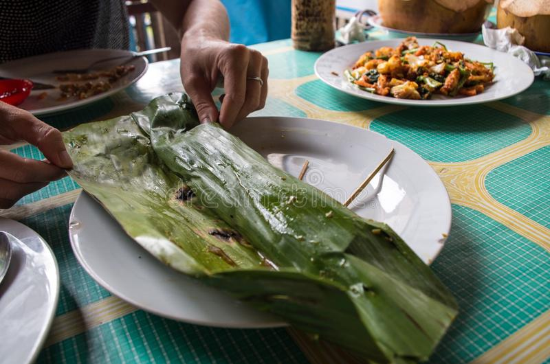 Indonesian dish PEPES IKAN from banana leaf on plate.  royalty free stock photography