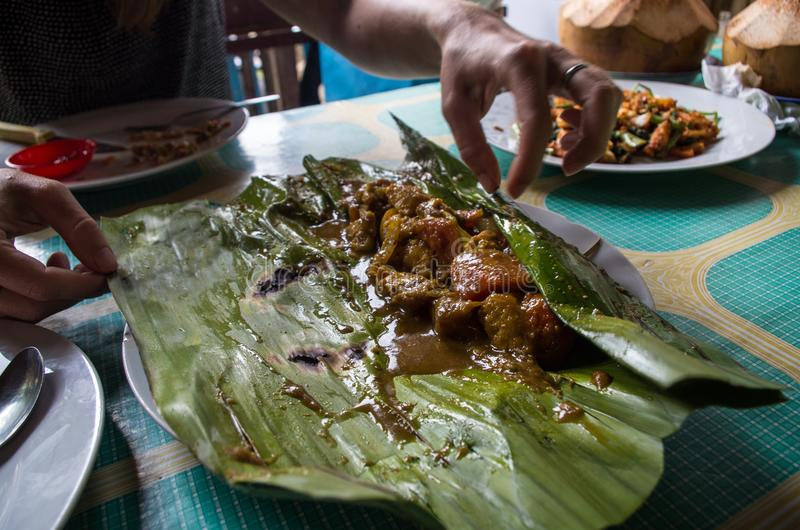 Indonesian dish - PEPES IKAN from banana leaf on plate.  stock photos