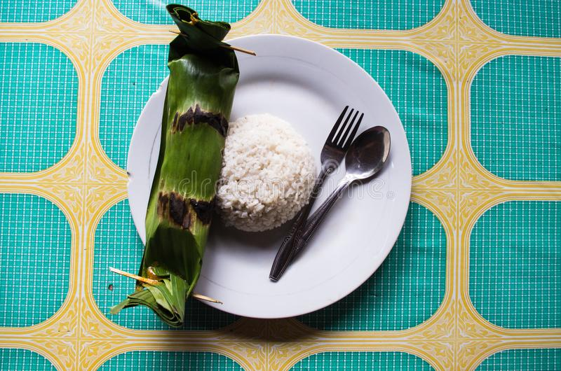 Indonesian dish PEPES IKAN closed in banana leaf - top view with rice.  stock photos