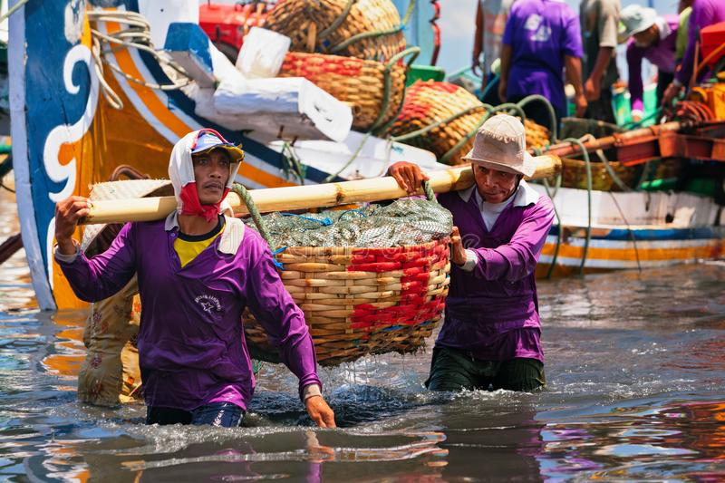Indonesian dockers unload traditional fishing boat royalty free stock image