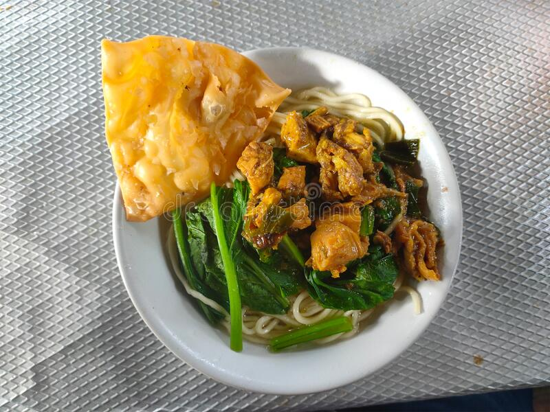 One bowl of chicken noodles (Mie Ayam) with fried wonton ready to be served on the table royalty free stock photos