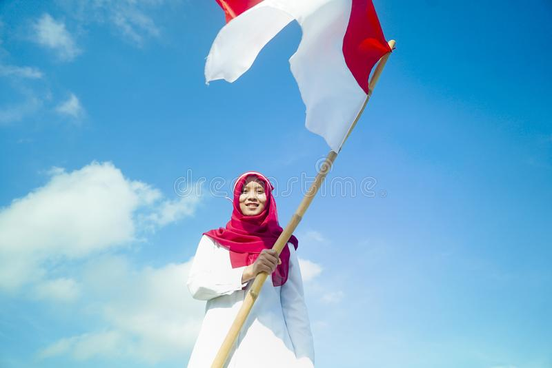 Girls pride flapping Indonesian flag with happiness with blu sky backgorund stock images
