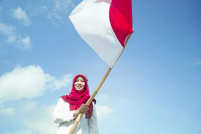 Girls pride flapping Indonesian flag with happiness with blu sky backgorund stock image