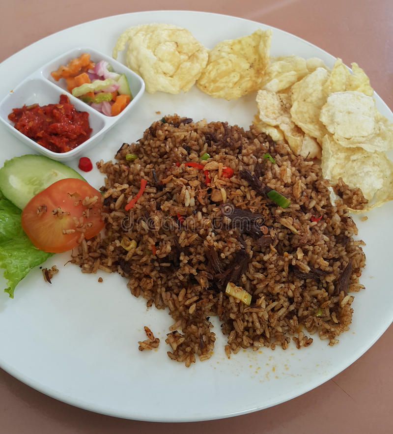 INDONESIAN FOOD FRIED RICE. Indonesian fried rice dish with lettuce, tomato, sliced cucumber, carrots, prawn crackers, anchovies and dried garlic royalty free stock photo