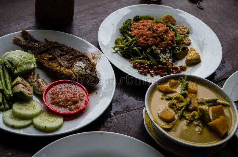 Indonesian food: Kankung plecing spicy water spinach dish, Ikan goreng fried fish and kare curry.  royalty free stock photos