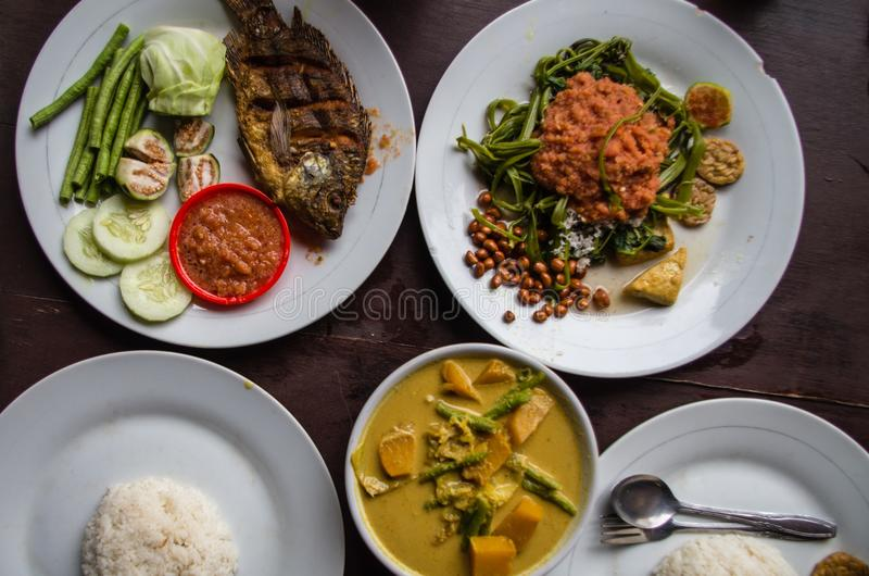 Indonesian food: Kankung plecing spicy water spinach dish, Ikan goreng fried fish and kare curry top view.  royalty free stock photography
