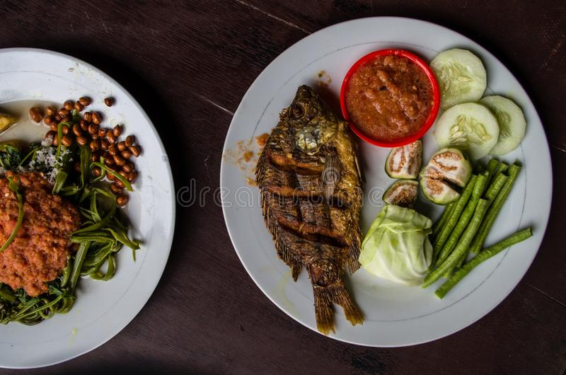 Indonesian food: Kankung plecing spicy water spinach dish and Ikan goreng fried fish top view.  royalty free stock image