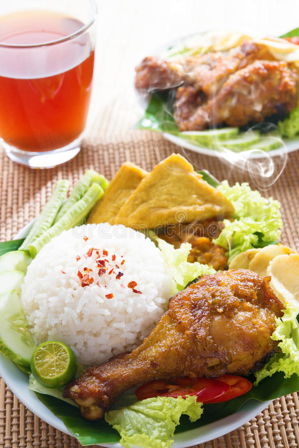 Indonesian food nasi ayam penyet. Popular Indonesian local food nasi ayam penyet, indonesian fried chicken rice. Fresh hot with steam smoke royalty free stock image