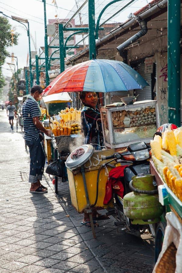 Indonesian food vendor hides from the rain, Ubud, Bali stock image