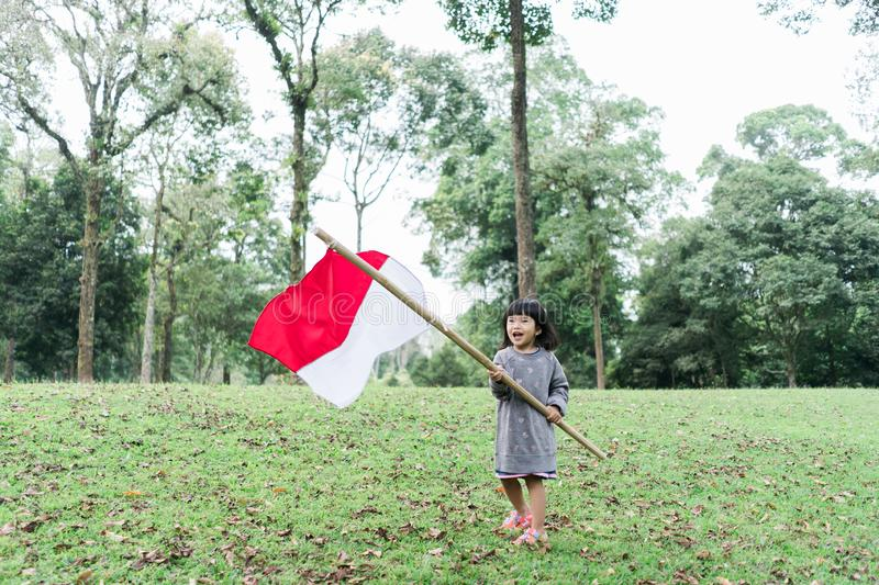 Indonesian girl holding bamboo stick with big flag. Of Indonesian in the park stock photo