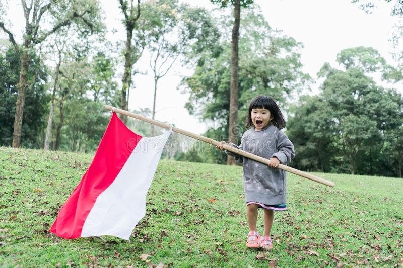 Indonesian girl holding bamboo stick with big flag. Of Indonesian in the park stock image