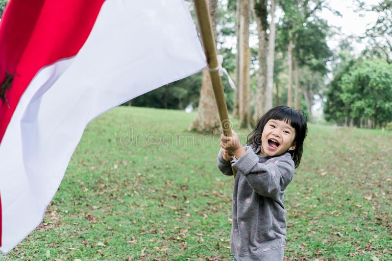 Indonesian girl holding bamboo stick with big flag. Of Indonesian in the park royalty free stock photo