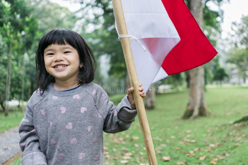 Indonesian girl holding bamboo stick with big flag. Of Indonesian in the park stock photography