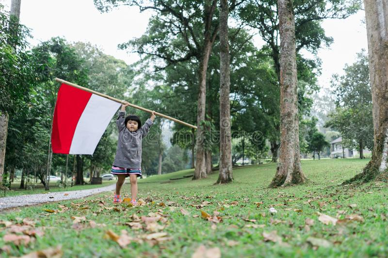 Indonesian girl holding bamboo stick with big flag. Of Indonesian in the park royalty free stock image