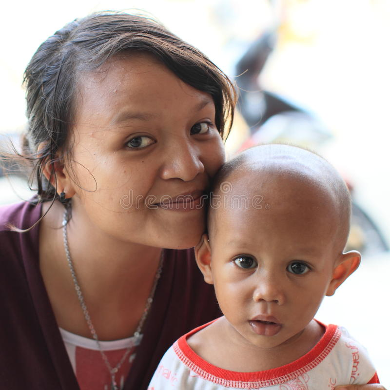 Indonesian girl kissing a baby stock images