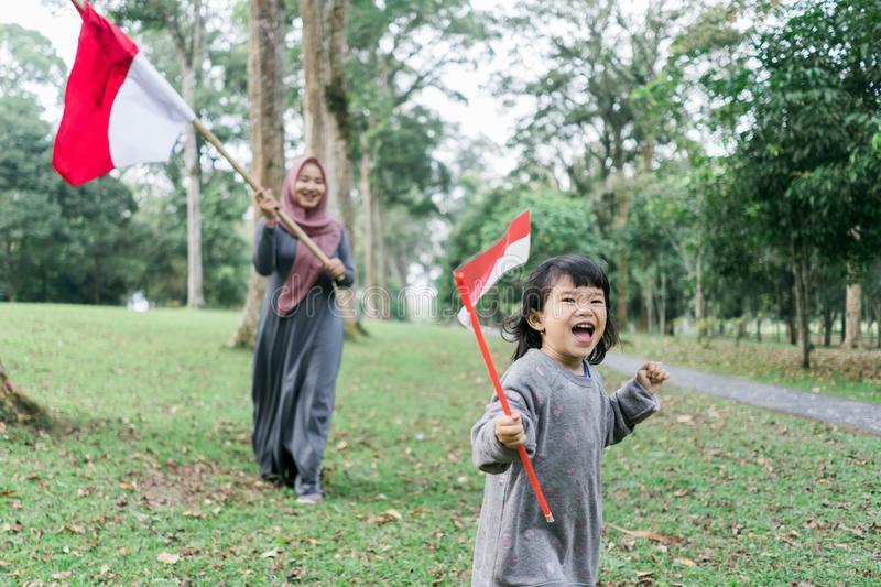 Indonesian hijab woman holding bamboo stick with big flag. Indonesian hijab mother and his daughter holding bamboo stick with big flag of Indonesian in the park stock photo