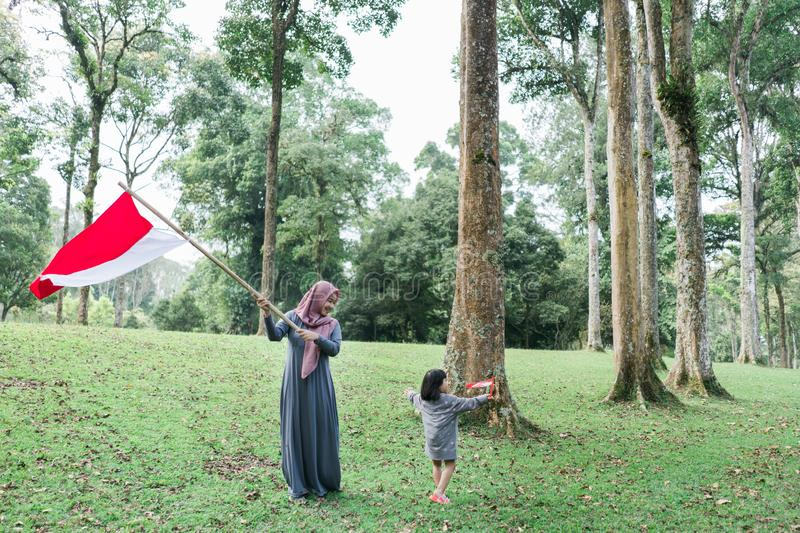 Indonesian hijab woman holding bamboo stick with big flag. Indonesian hijab mother and his daughter holding bamboo stick with big flag of Indonesian in the park stock photos