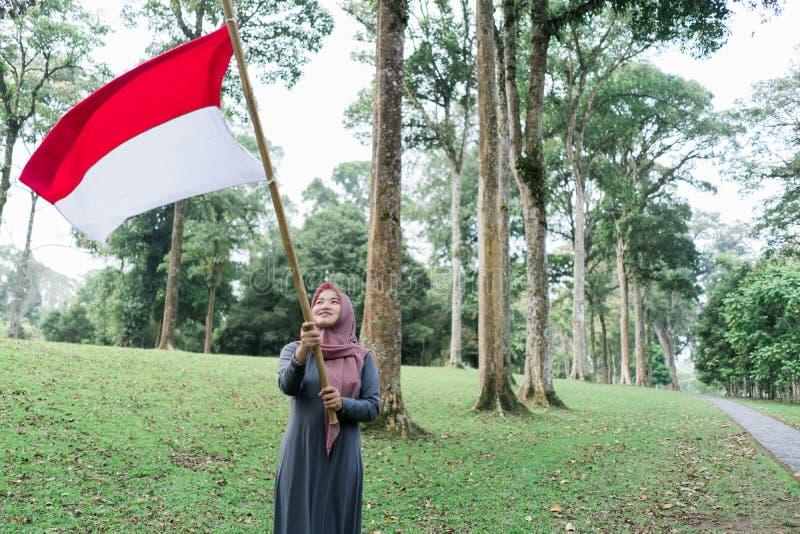 Indonesian hijab woman holding bamboo stick with big flag. Indonesian hijab women holding bamboo stick with big flag of Indonesian in the park royalty free stock image