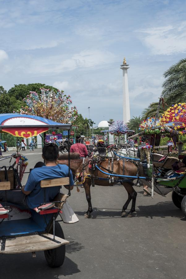 Indonesian horse carriages` drivers wait at Merdeka Square with the National Monument in the background in Jakarta, Indonesia. stock image