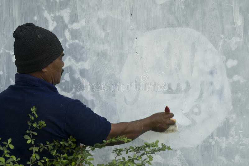 INDONESIAN INTELLIGENCE TO WATCH EXTREMIST GROUP ON ISLAMIC STATE ISSUES. Government officials are erasing graffiti of Islamic State (ISIS) banner in Solo, Java royalty free stock photo