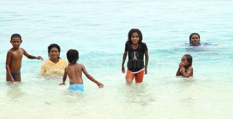 Indonesian kids playing in sea. Indonesian kids (boys and girls) and adult women in wet clothes playing in sea (Manokwari, Papua Barat, Indonesia royalty free stock photo