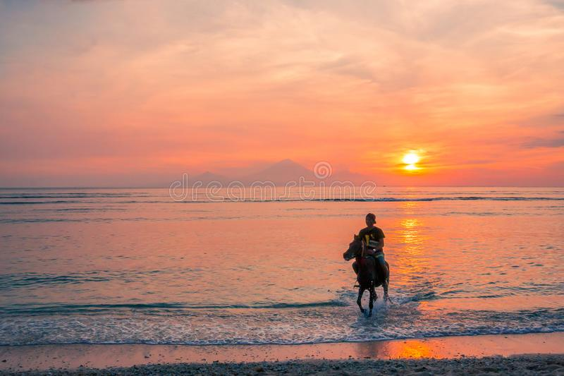 An indonesian man riding in the water at sunset stock images