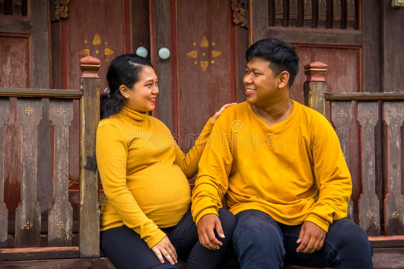 Indonesian pregnant wife sits with her husband outside their traditional house. An Indonesian pregnant wife chatting with her husband, sitting on the porch stock image