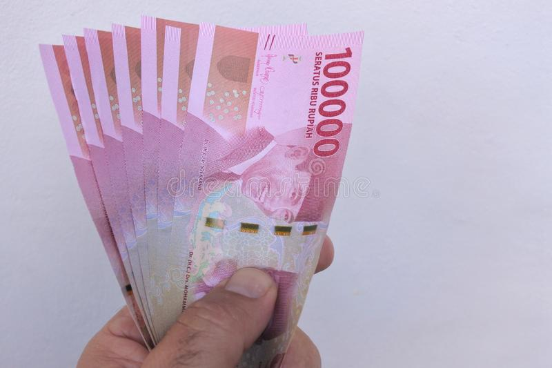 Indonesian rupiah currency of Indonesia. Man holding 100,000 Indonesian rupiah currency of Indonesia bank notes stock photography