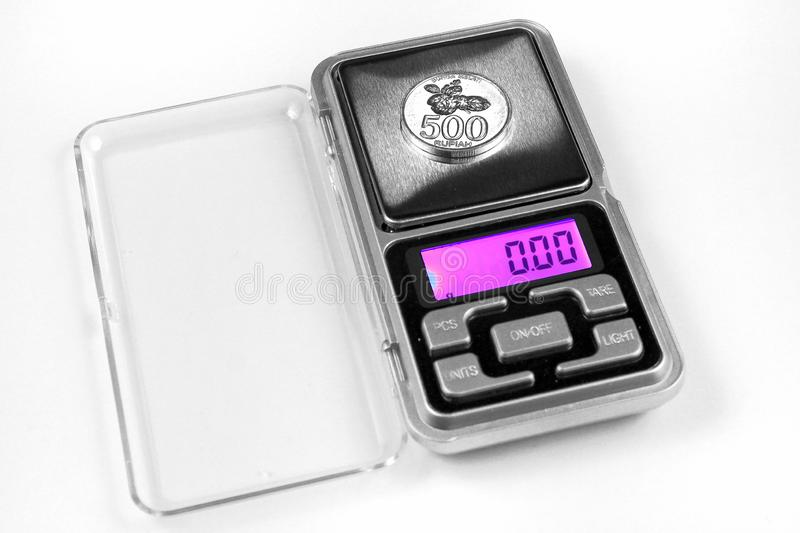 500 Indonesian rupiahs coin on scales, shows zero weight. Currency inflation concept stock photos
