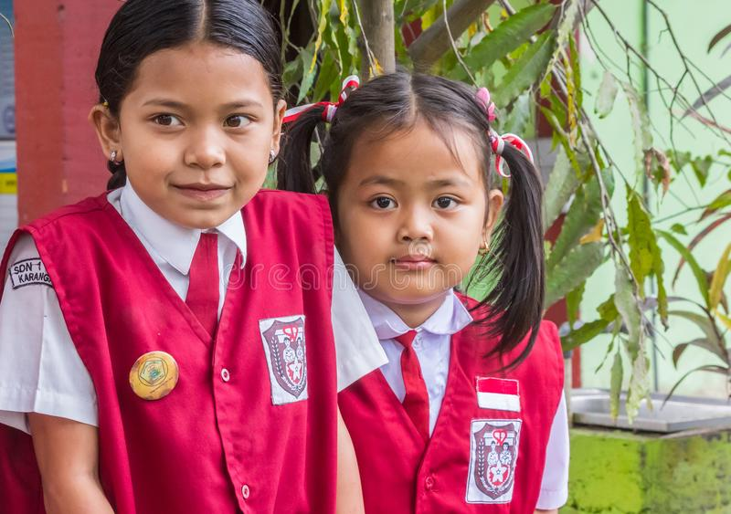 Indonesian schoolgirls in uniform posing in front of their school. Near Amed, Bali, Indonesia stock image