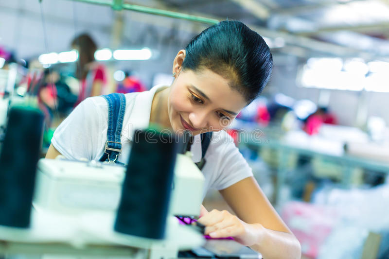 Indonesian seamstress in a textile factory stock images